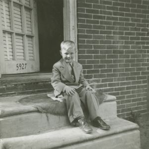 Author on the front stoop of the mill house at 5927 Angora Terrace, c. 1950